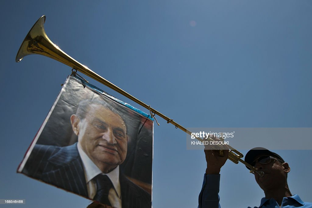 A supporter of former Egyptian president Hosni Mubarak, hangs his portrait on a trumpet outside the Egyptian police academy in Cairo, where Mubarak's trial is taking place on May 11, 2013. Mubarak appeared in court to face a new trial for complicity in the murder of hundreds protesters during the 2011 uprising. AFP PHOTO / KHALED DESOUKI