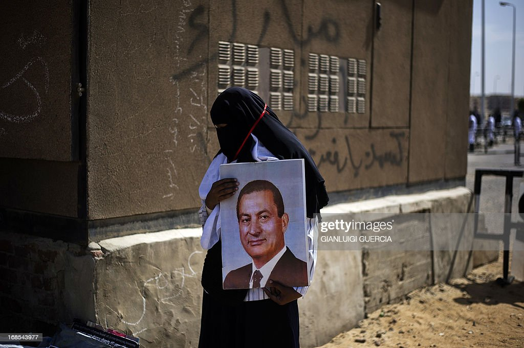 A Supporter of former Egyptian president Hosni Mubarak, hold his portrait and shout slogans outside the Egyptian police academy in Cairo, where Mubarak's trial is taking place on May 11, 2013. Former Egyptian president Hosni Mubarak appeared in court to face a new trial for complicity in the murder of hundreds protesters during the 2011 uprising.