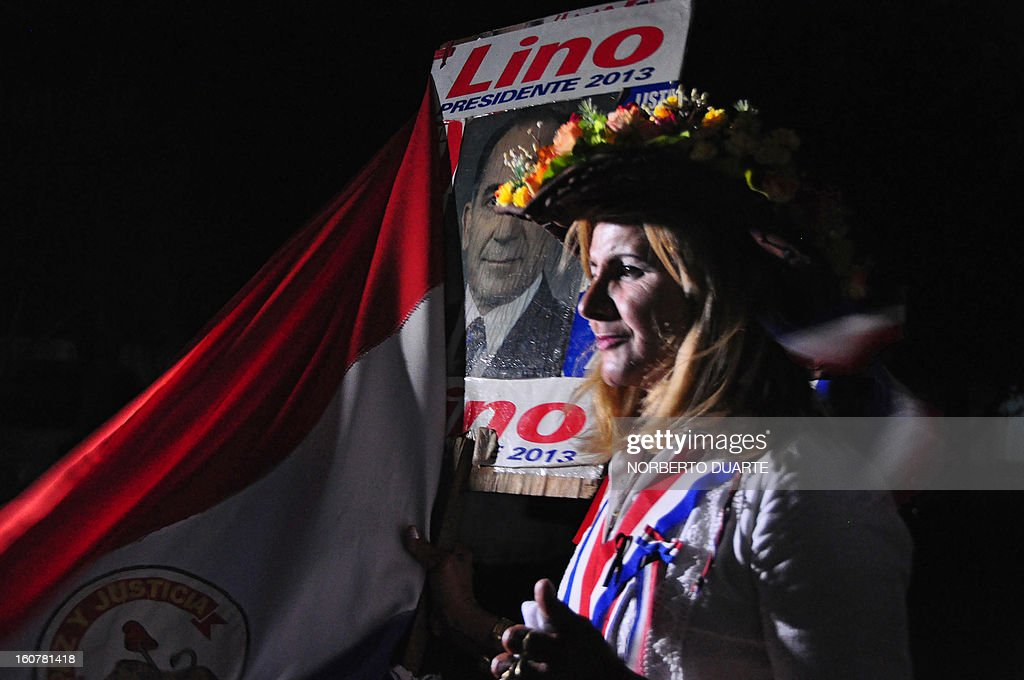 A supporter of former general and UNACE party presidential candidate Lino Oviedo --who died along with his bodyguard Denis Galeano and pilot Ramon Picco Delmas in a helicopter crash on February 2-- arrives with a portrait of him and a flag to his home in Luque, Paraguay on February 5, 2013, where his wake will take place. Oviedo, 69, the controversial presidential candidate who helped topple Paraguayan dictator Alfredo Stroessner in 1989, died when the aircraft crashed en route to Asuncion while returning from a campaign rally in northern Paraguay, prompting claims of foul play.