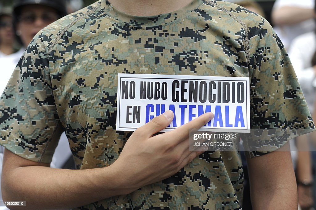 A supporter of former Guatemalan de facto President (1982-1983), retired General Jose Efrain Rios Montt, holds a sign reading 'There was no genocide in Guatemala' during a protest against the latter's prosecution, outside a military prison at Matamoros in Guatemala City on May 12, 2013. Rios Montt was found guilty of genocide and war crimes on May 10 and sentenced to 80 years in prison in a landmark ruling stemming from massacres of indigenous people in his country's long civil war. Rios Montt thus became the first Latin American convicted of trying to exterminate an entire group of people in a brief but particularly gruesome stretch of a war that started in 1960, lasted 36 years and left around 200,000 people dead or missing. AFP PHOTO / Johan ORDONEZ
