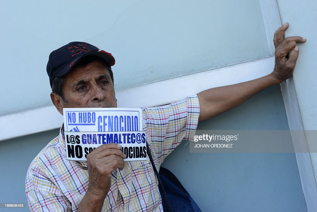 A supporter of former Guatemalan de facto President (1982-1983) retired General Jose Efrain Rios Montt holds a sign reading 'The Guatemalans we are not genocidal' during a protest against the latter's prosecution, outside the Constitutional Court in Guatemala City on May 15, 2013. Rios Montt was found guilty of genocide and war crimes on May 10 and sentenced to 80 years in prison in a landmark ruling stemming from massacres of indigenous people in his country's long civil war. Rios Montt thus became the first Latin American convicted of trying to exterminate an entire group of people in a brief but particularly gruesome stretch of a war that started in 1960, lasted 36 years and left around 200,000 people dead or missing. AFP PHOTO / Johan ORDONEZ