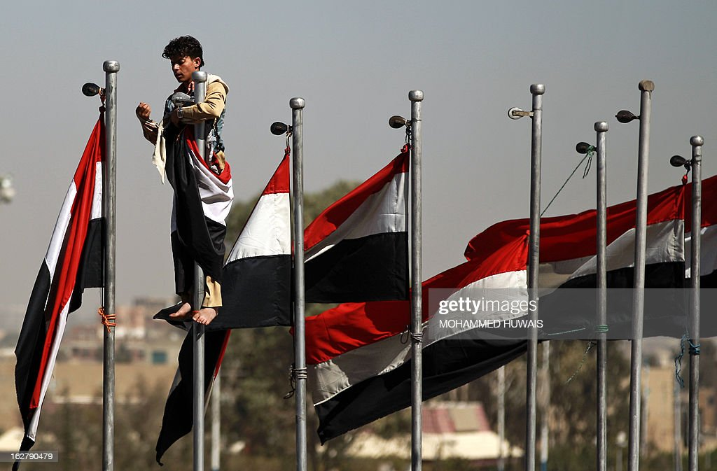 A supporter of former Yemeni president Ali Abdullah Saleh climbs up a flag pole flying his national flag during celebrations on the occasion of the first anniversary of the handover of power in Sanaa on February 27, 2013. Saleh stepped down after 33-years at the helm in February 2011 and formally handed power to his then deputy, Abdrabuh Mansur Hadi.
