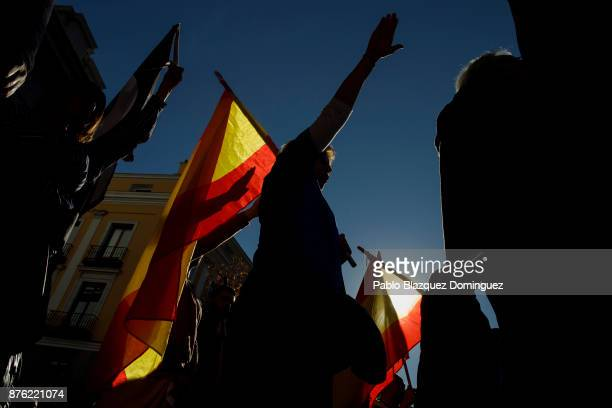 A supporter of Franco does a fascist salute as she holds a Spanish flag during a rally commemorating the 42nd anniversary of Spain's former dictator...