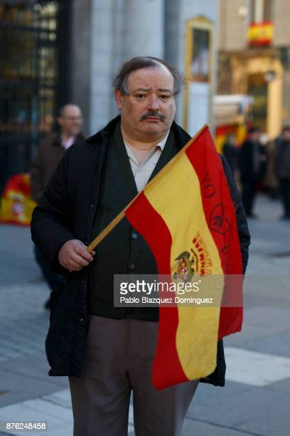 A supporter of Franco looks on as he holds a preconstitutional Spanish flag during a rally commemorating the 42nd anniversary of Spain's former...
