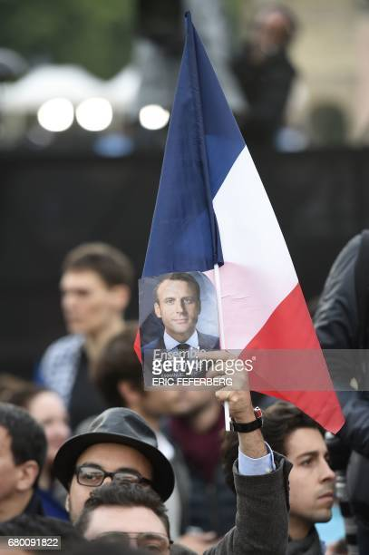 A supporter of French presidentelect Emmanuel Macron holds a portrait of Macron and waves a French national flag as he celebrates at the Louvre...