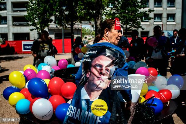 TOPSHOT A supporter of French presidential candidate for the En Marche movement Emmanuel Macron stands with a campaign poster wrapped around her...