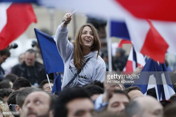TOPSHOT A supporter of French presidential election candidate for the En Marche movement Emmanuel Macron celebrates in front of the Pyramid at the...