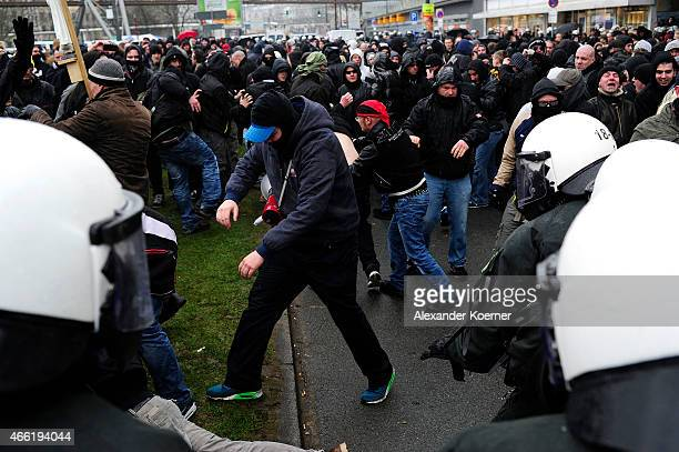Supporter of HoGeSa clash with riot police forces during a rally of Pegida on March 14 2015 in Wuppertal Germany Several hundred Salafis who in...