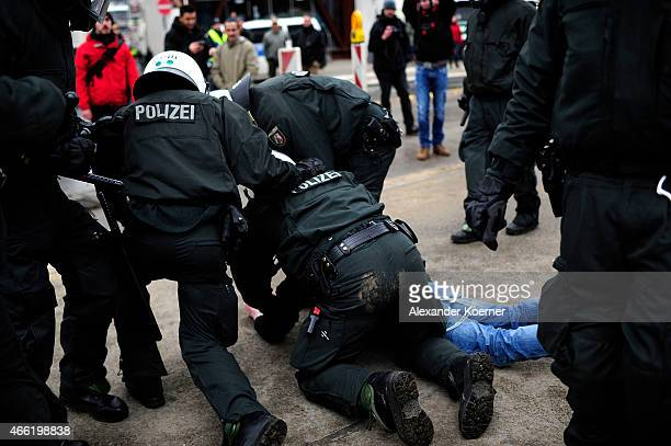 A supporter of HoGeSa is tackled down by riot police forces during a rally of Pegida on March 14 2015 in Wuppertal Germany Several hundred Salafis...