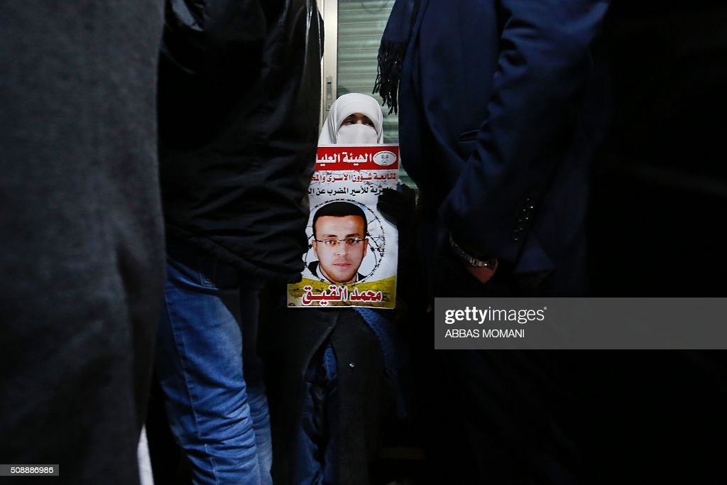 A supporter of hunger striking Palestinian prisoner Mohammed al-Qiq holds a portrait as she demonstrates in solidarity with him on February 7, 2016, outside the International Committee of the Red Cross (ICRC) offices in the West Bank city of Ramallah. Qiq will keep up his 10-week hunger strike despite Israel suspending a detention without trial order against him, his lawyer said on February 5. / AFP / ABBAS MOMANI