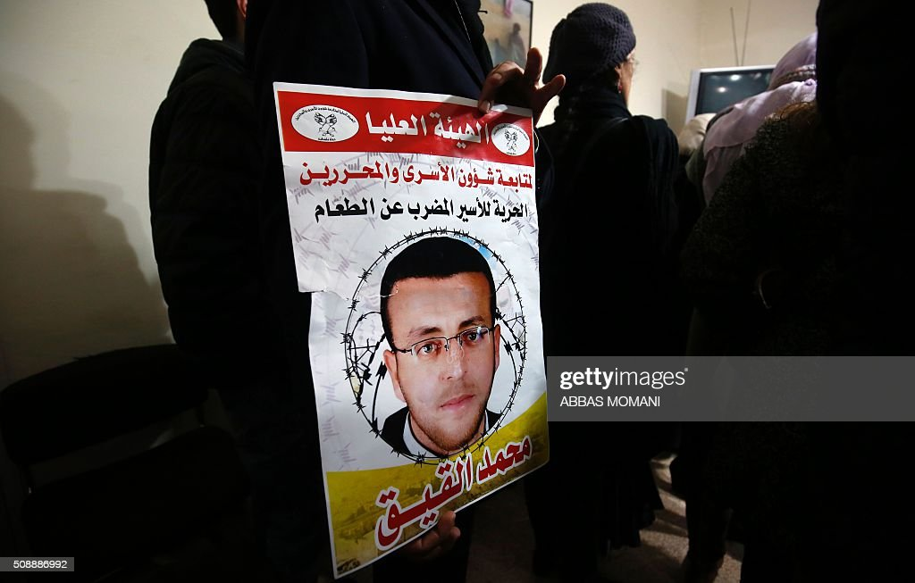 A supporter of hunger striking Palestinian prisoner Mohammed al-Qiq holds a portrait as he demonstrates in solidarity with him on February 7, 2016, outside the International Committee of the Red Cross (ICRC) offices in the West Bank city of Ramallah. Qiq will keep up his 10-week hunger strike despite Israel suspending a detention without trial order against him, his lawyer said on February 5. / AFP / ABBAS MOMANI