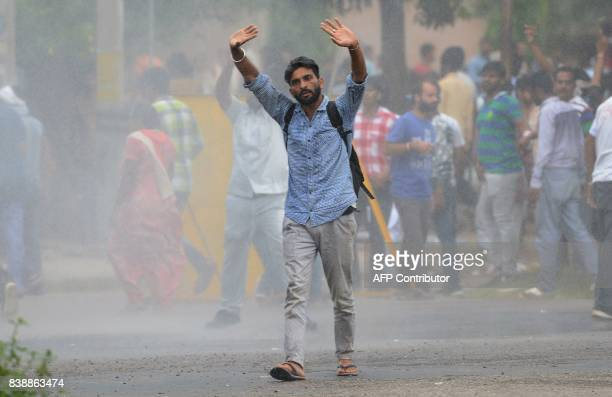 A supporter of Indian religious leader Gurmeet Ram Rahim Singh gestures towards security forces during clashes in Panchkula on August 25 2017 At...