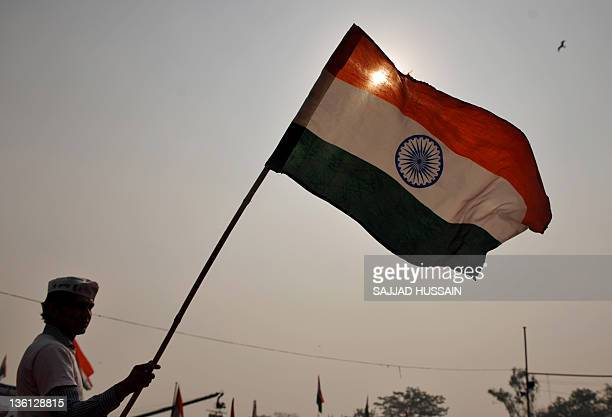 A supporter of Indian social activist Anna Hazare waves a national flag during a rally in Ram Lila Ground in New Delhi on December 272011 The...