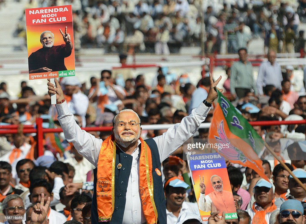 A supporter of India's Bharatiya Janta Party (BJP) wears a mask with an image of the Chief Minister of the western Indian state of Gujarat Narendra Modi as he participates in Modi's swearing in ceremony at The Sardar Patel Navrangpura Stadium in Ahmedabad on December 26, 2012. Modi who won a landslide victory in recent state assembly polls, was administered the oath of office and secrecy by Gujarat Governor Kamla Beniwal at a ceremony which was attended by many senior BJP leaders. AFP PHOTO/Sam PANTHAKY