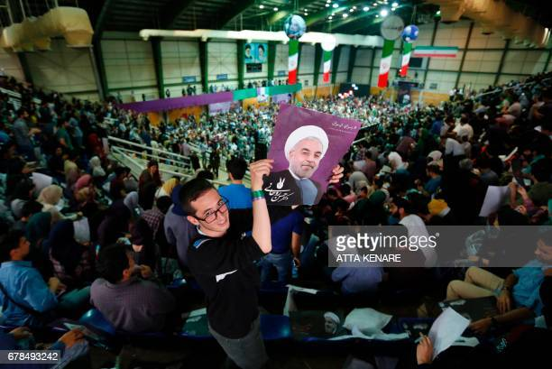 A supporter of Iranian presidential candidate Hassan Rouhani holds up his portrait during a campaign rally in the capital Tehran on May 4 2017 / AFP...