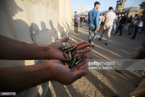 A supporter of Iraqi cleric Moqtada alSadr carries bullet casings following clashes with security forces after they broke into Baghdad's fortified...