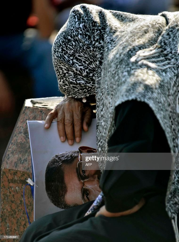 A supporter of Islamist Egyptian President Mohamed Morsi leans her head against a post as she holds his image during a rally outside Cairo University, on June 2, 2013. A top Muslim Brotherhood leader urged Egyptians to stand ready to sacrifice their lives to prevent a coup, after the army gave Islamist President Mohamed Morsi and his opponents until July 3 to resolve their differences or face intervention.