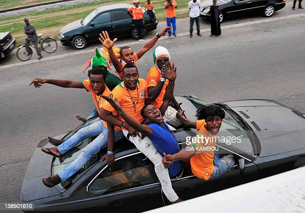 Supporter of Ivory Coast's football team parade ontop of a car as they wait for the team's arrival on the road to the Felix Houphouet Airport in...