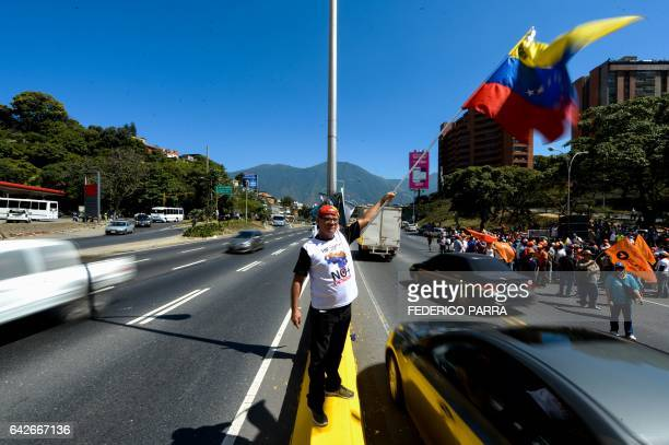 A supporter of jailed Venezuelan opposition leader Leopoldo Lopez waves a Venezuelan flag during a demonstration held on the third anniversary of his...