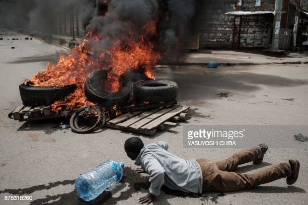 A supporter of Kenyan's opposition party National Super Alliance reacts next to a burning tyre barricade during a demonstration on November 17 2017...