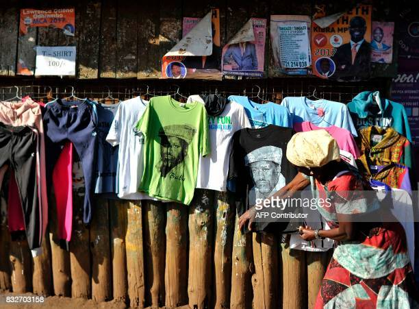 A supporter of Kenya's embattled opposition leader Raila Odinga looks at a Tshirt bearing a portrait of him displayed for sale on a street on August...