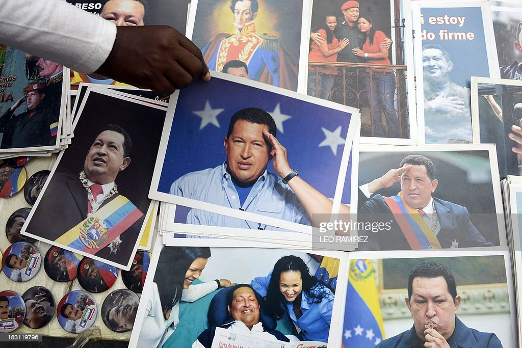 A supporter of late Venezuelan President Hugo Chavez holds a picture of the leader during the commemoration of the first anniversary of his last presidential campaign in Caracas on September 4, 2013. AFP PHOTO/Leo RAMIREZ