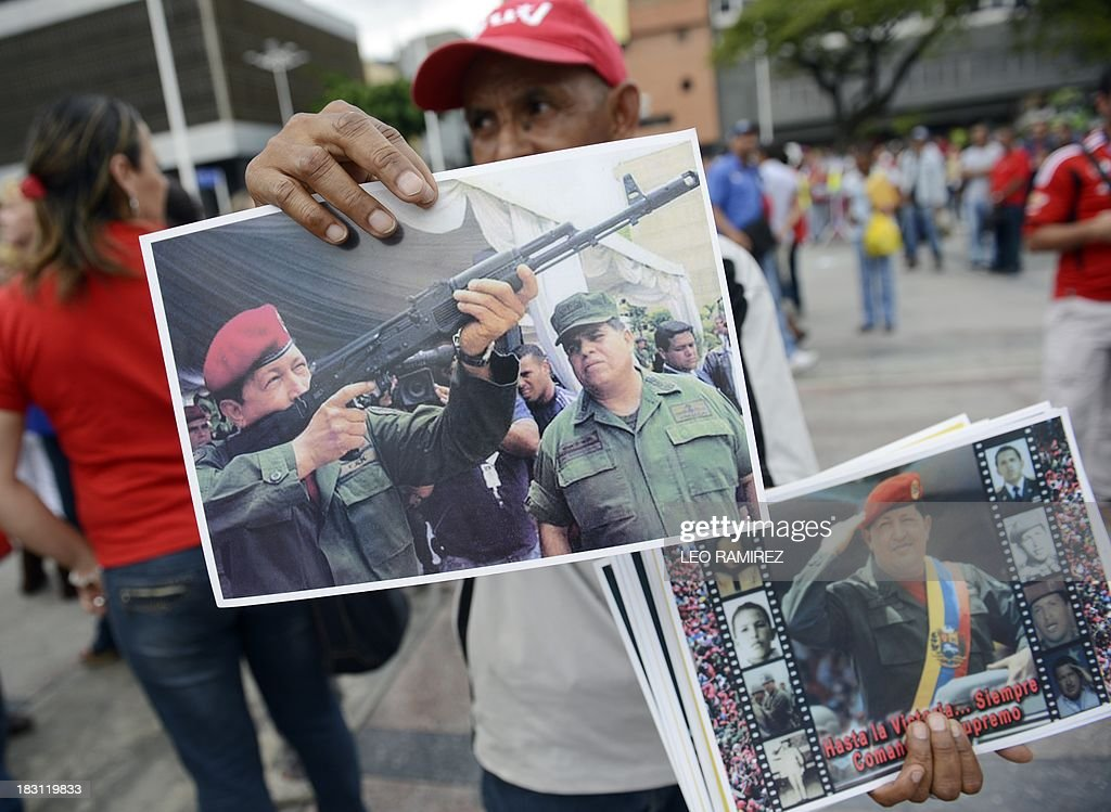 A supporter of late Venezuelan President Hugo Chavez shows pictures of the leader during the commemoration of the first anniversary of his last presidential campaign in Caracas on September 4, 2013. AFP PHOTO/Leo RAMIREZ