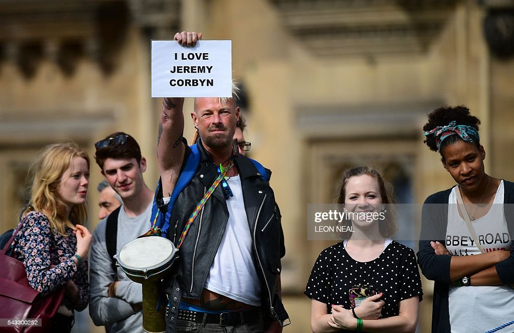 A supporter of Leader of the opposition Labour Party Jeremy Corbyn holds up a placard outside parliament in central London on June 27, 2016. Britain's historic decision to leave the 28-nation bloc has sent shockwaves through the political and economic fabric of the nation. It has also fuelled fears of a break-up of the United Kingdom with Scotland eyeing a new independence poll, and created turmoil in the opposition Labour party where leader Jeremy Corbyn is battling an all-out revolt. / AFP / Leon NEAL