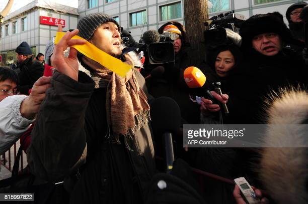 A supporter of leading Chinese dissident Liu Xiaobo holds a yellow ribbon while sepaking to the media outside the courthouse following the verdict...