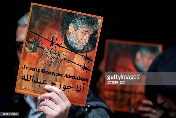 A supporter of Lebanese militant Georges Ibrahim Abdallah holds up a placard bearing his portrait and a slogan in French and Arabic reading 'I am...