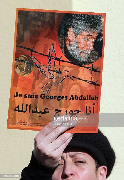 A supporter of Lebanese militant Georges Ibrahim Abdallah shows a placard during a protest outside the French embassy in Beirut against the decision...