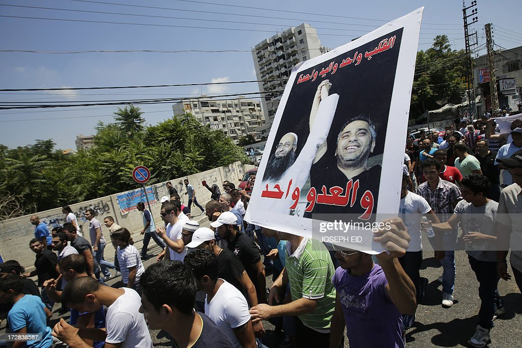 A supporter of Lebanese radical cleric Ahmad al-Assir raises a poster of him holding hands with Lebanese singer Fadel Shaker (R) as they demonstrate after Friday prayers in the Abra district of the southern Lebanese city of Sidon on July 5, 2013. Assir, a radical Salafi on the run since deadly clashes between his forces and the country's army last month, urged his supporters to turn out to a Friday rally.
