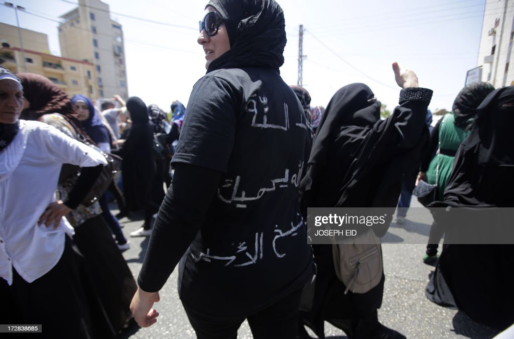 A supporter of Lebanese radical cleric Ahmad al-Assir wears a t-shirt with text on it reading in Arabic: 'Lion of Sunni Sheikh Ahmed al-Assir, may God protect you' as they demonstrate in support of him after Friday prayers in the Abra district of the southern Lebanese city of Sidon on July 5, 2013. Assir, a radical Salafi on the run since deadly clashes between his forces and the country's army last month, urged his supporters to turn out to a Friday rally.
