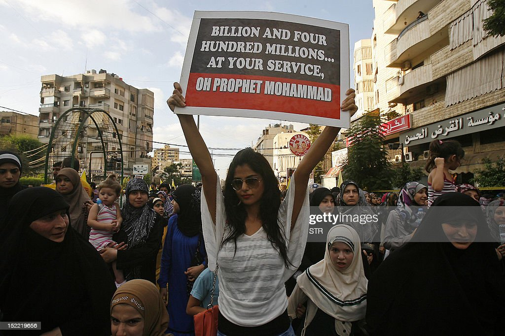 A supporter of Lebanon's Hezbollah group holds a sign as she marches with others during a rally in southern Beirut to denounce a film mocking Islam on September 17, 2012. Hezbollah chief Hassan Nasrallah, who made a rare public appearance at the rally, has called for a week of protests across the country over the low-budget, US-made film, describing it as the 'worst attack ever on Islam.' AFP PHOTO / STR