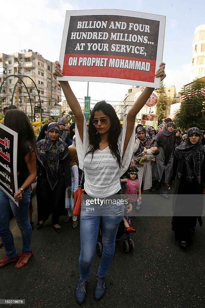 A supporter of Lebanon's Hezbollah group holds a sign as she marches with others during a rally in southern Beirut to denounce a film mocking Islam on September 17, 2012. Hezbollah chief Hassan Nasrallah, who made a rare public appearance at the rally, has called for a week of protests across the country over the low-budget, US-made film, describing it as the 'worst attack ever on Islam.'