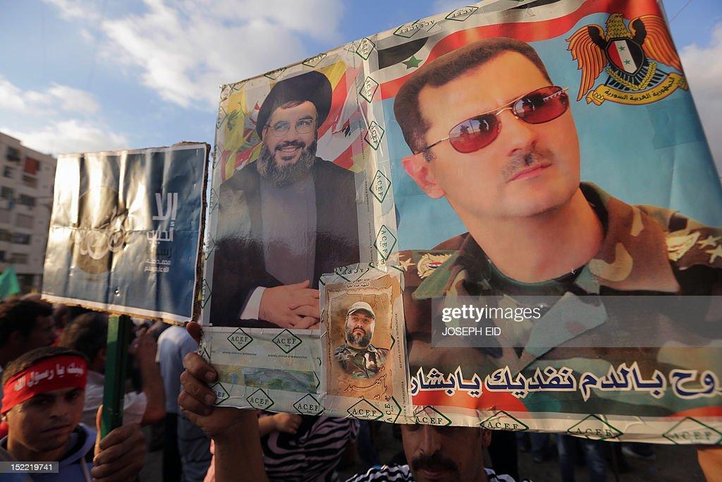 A supporter of Lebanon's Hezbollah group holds pictures of Hezbollah chief Hassan Nasrallah Syrian President Bashar alAssad and slain Hezbollah...
