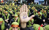 A supporter of Lebanon's militant Shiite Muslim movement Hezbollah shows his hand reading in Arabic 'answering your call [Hussein]' during a parade...
