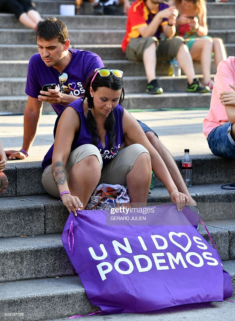 A supporter of left wing party Podemos display a Podemos flag on the ground during Spain's general elections in Madrid on June 26, 2016. Spain's ruling conservative Popular Party (PP) took first place in a repeat general election on June 26 but fell well short of a majority while far-left formation Unidos Podemos came second, an exit poll showed. / AFP / GERARD