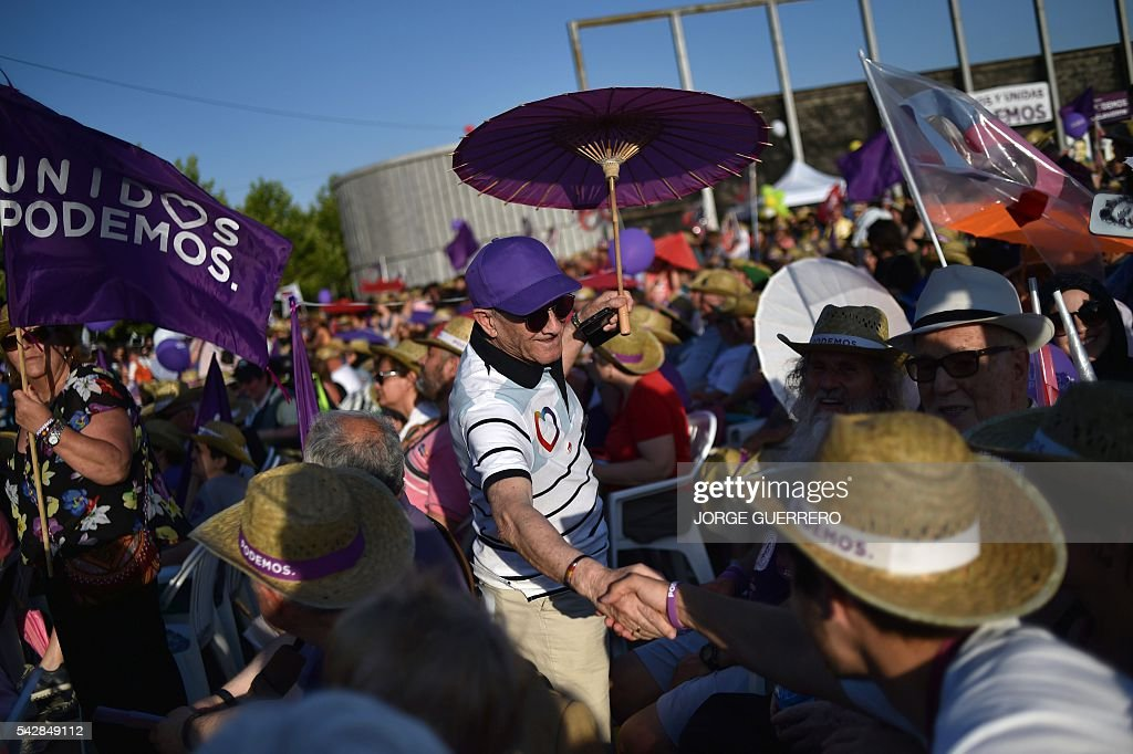 A supporter of left wing party Podemos with a sun umbrella shakes hands with another man before the partys final campaign meeting in Madrid on June 24, 2016 ahead of the June 26 general election. Spain votes again on June 26, six months after an inconclusive election which saw parties unable to agree on a coalition government. GUERRERO