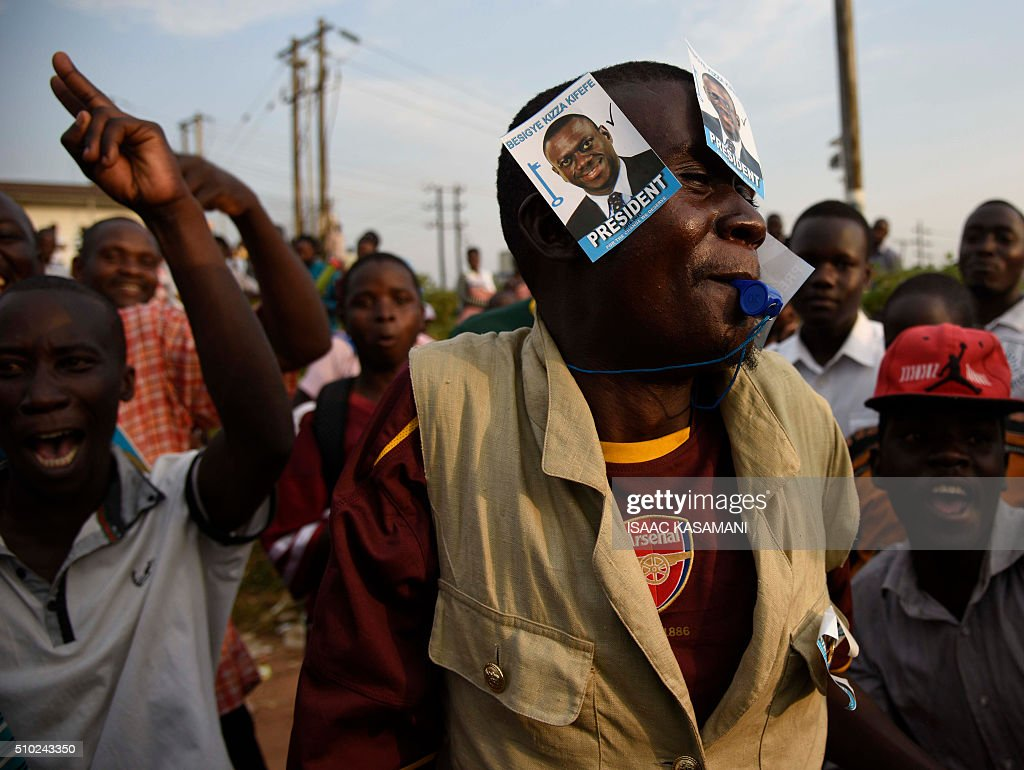 A supporter of main opposition presidential candidate Kizza Besigye from the Forum for Democratic Change (FDC) party, wears stickers depicting the leader, during a political rally in Wakiso District, in Kampala on February 14, 2016, two days before the Uganda's Presidential elections. Incumbent President Museveni is facing the hardest fight to keep his office as his main rival Kizza Besigye and his former Prime Minister Amama Mbabazi have gained country wide support. / AFP / ISAAC KASAMANI