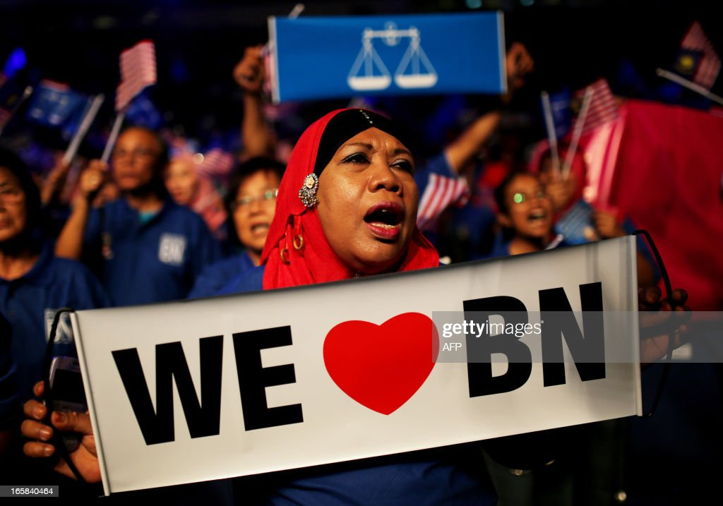 A supporter of Malaysia's ruling National Front coalition, or Barisan Nasional, waves a banner during Malaysia's Prime Minister Najib Razak's launch of his election manifesto at the National Stadium in Bukit Jalil, a suburb of Kuala Lumpur, on April 6, 2013. Malaysia's premier Najib Razak unveiled a manifesto on April 6 pledging bigger cash handouts, millions of new jobs and lower taxes and crime, as he seeks his first mandate in looming national polls. AFP PHOTO / MOHD RASFAN