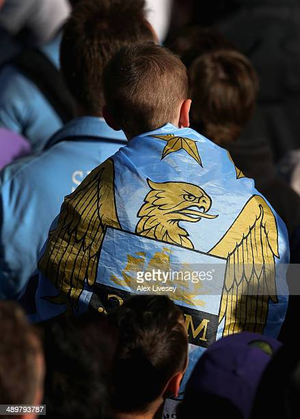 A supporter of Manchester City waits outside Manchester Town Hall prior to the start of the Manchester City victory parade around the streets of...