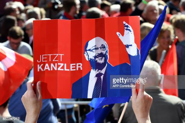 A supporter of Martin Schulz leader of Germany's social democratic SPD party and candidate for Chancellor holds up a poster supporting the SPD's top...
