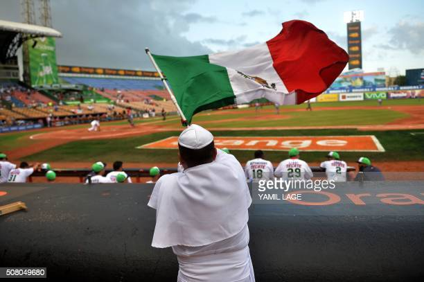 TOPSHOT A supporter of Mexico disguised as Pope Francis flutters a Mexican flag during their 2016 Caribbean baseball series game against Cuba on...
