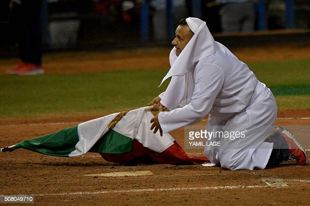 A supporter of Mexico disguised as Pope Francis holds a Mexican flag during their 2016 Caribbean baseball series game against Cuba on February 2 2016...