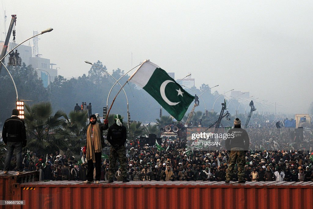 A supporter of moderate preacher Tahir-ul Qadri waves the Pakistani national flag on the third day of a protest rally in Islamabad on January 16, 2013. Pakistani protesters rallied for a third day January 16 in the largest political demonstration seen for years in the capital, calling on the government to quit after the Supreme Court ordered the arrest of the prime minister. AFP PHOTO/Asif HASSAN