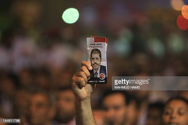 A supporter of Mohammed Mursi the Muslim Brotherhood's candidate in Egypt's presidential election holds a leaflet depicting Mohammed Mursi during a...