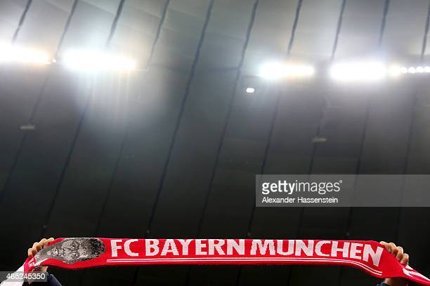 A supporter of Muenchen holds up a FC Bayern Muenchen fan scarf during the round of 16 DFB Cup match between FC Bayern Muenchen and Eintracht...