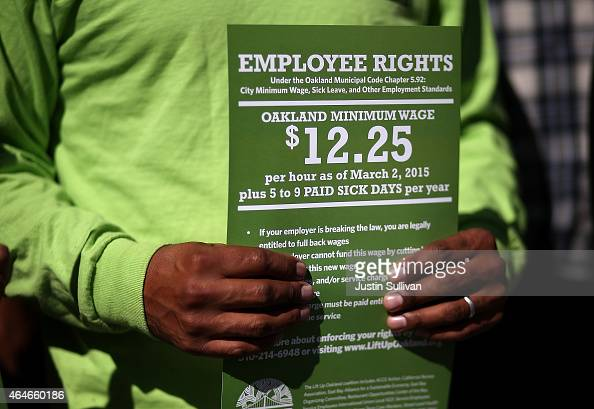 A supporter of Oakland's minimum wage increase holds a sign during a celebration rally outside of Oakland City Hall on February 27 2015 in Oakland...
