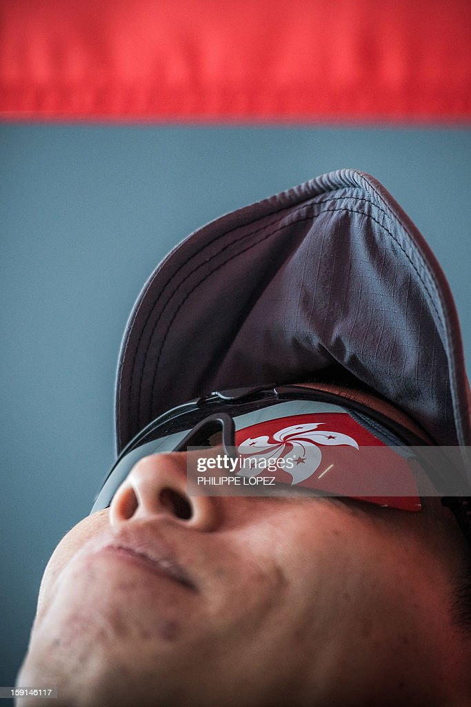 A supporter of of Hong Kong Chief Executive Leung Chun-ying looks up as he holds a Hong Kong flag while standing against pro-democracy supporters during a protest in Hong Kong on January 9, 2013. Pro-democracy lawmakers were expected to table an impeachment motion on January 9 against chief executive Leung Chun-ying, demanding him to quit over a housing scandal. AFP PHOTO / Philippe Lopez